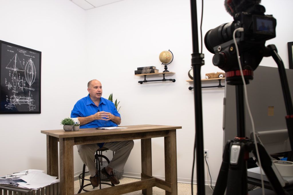 Man in blue shirt talking while sitting at desk and being filmed by camera