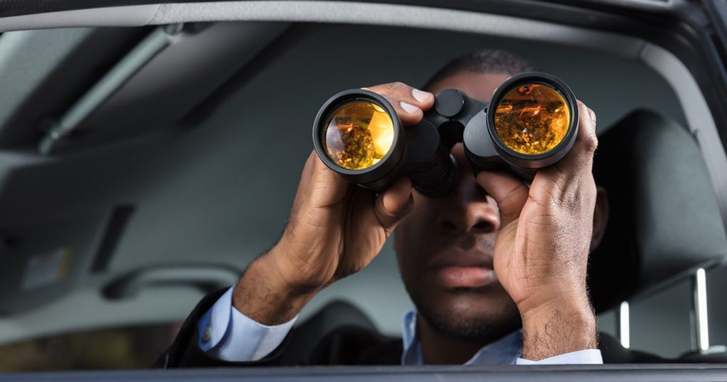 Man in car wearing suit holding binoculars up to his face