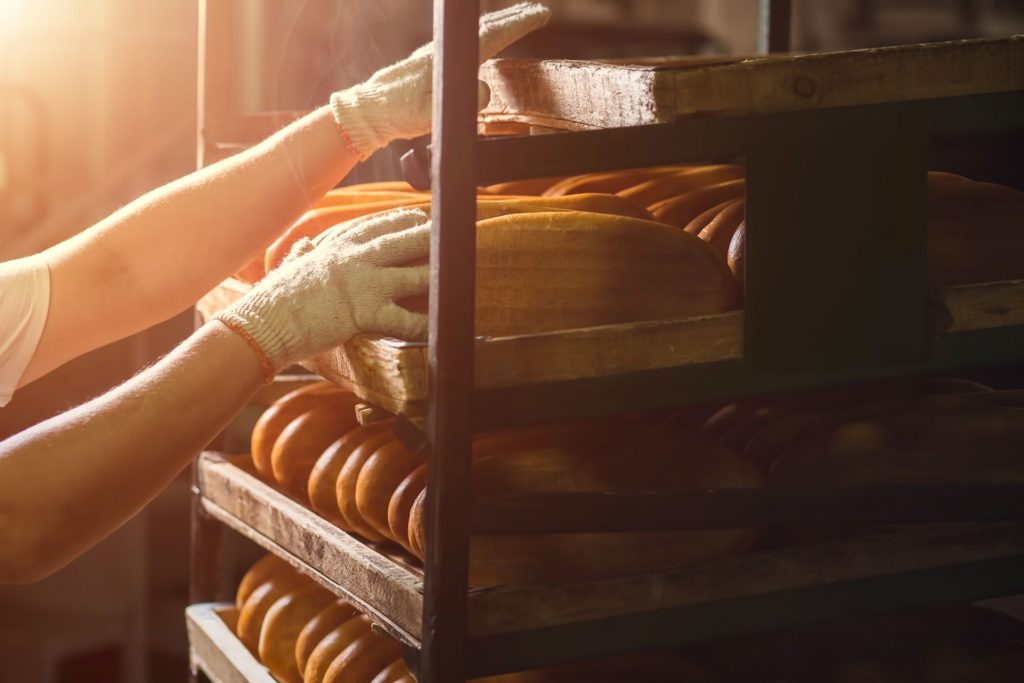 baker's gloved hands touching bread on racks in bakery