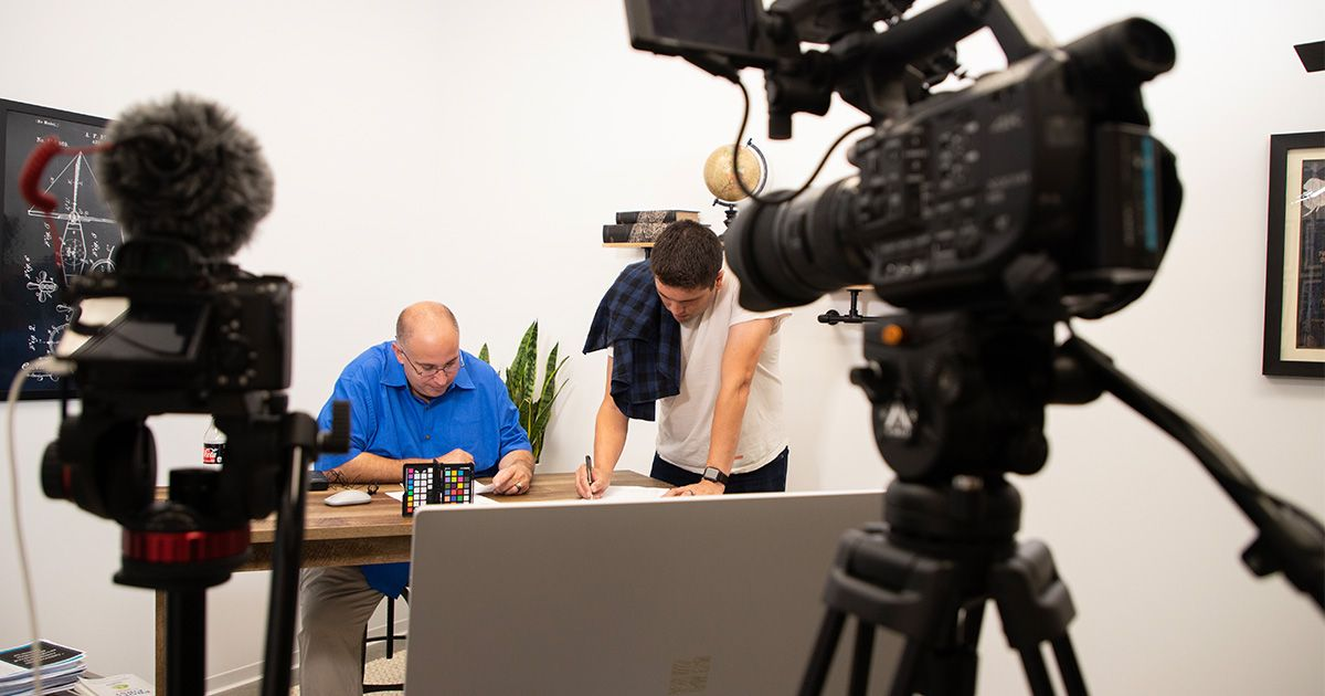 Kevin King and Bradley looking at papers on desk with camera recording them in foreground