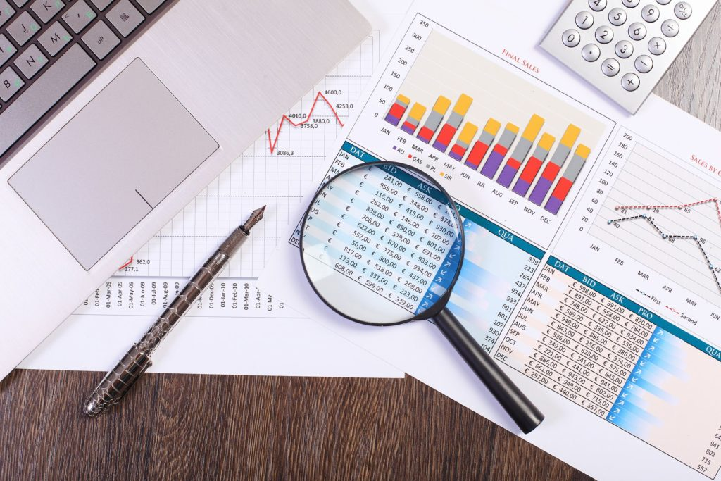 Magnifying glass, pen, laptop, and calculator on printed spreadsheets and charts