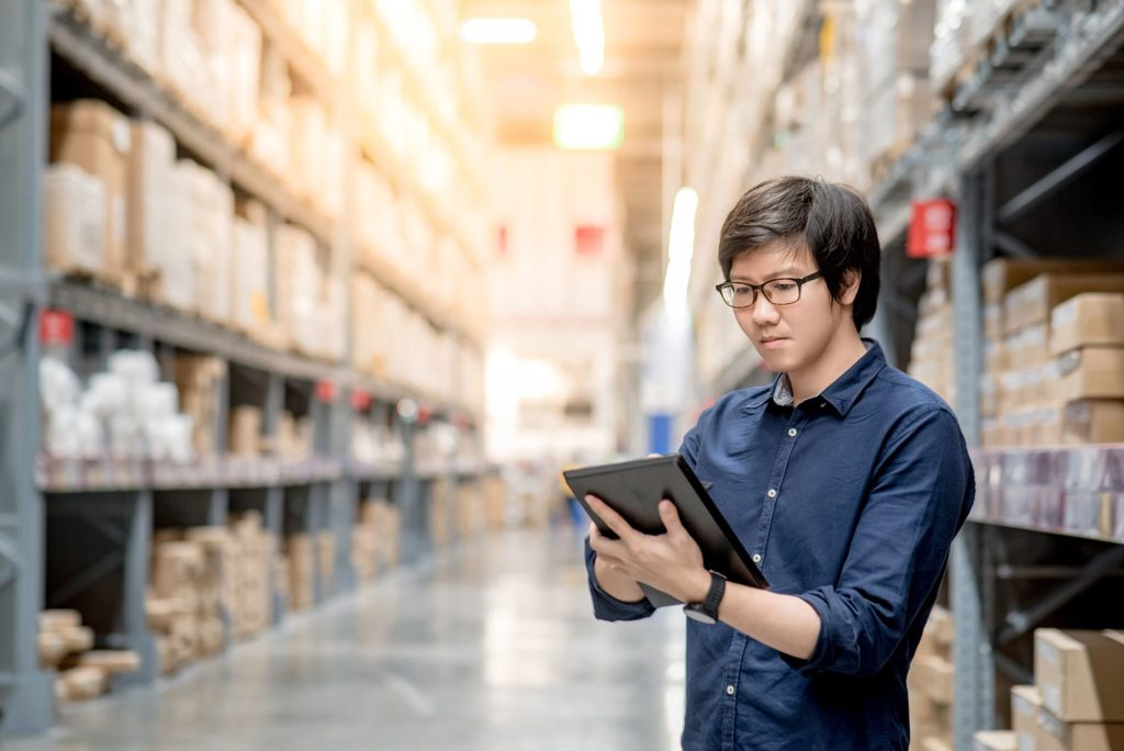 Man with dark blue shirt and glasses reading a tablet while standing inside a warehouse
