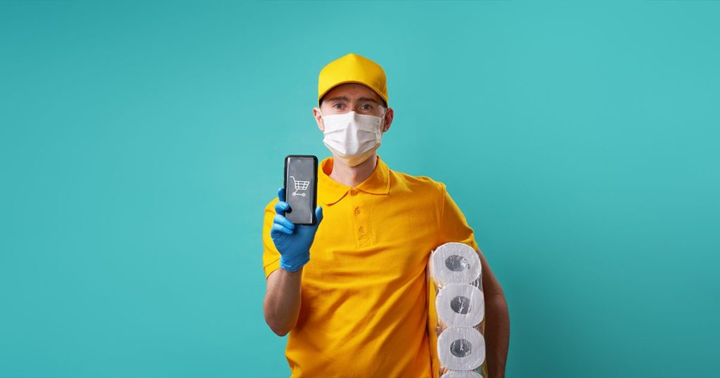 Courier dressed in yellow with gloves and mask, holding toilet paper and phone