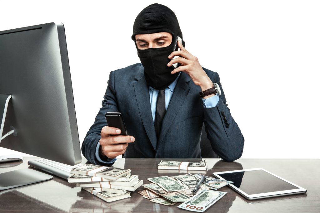 businessman wearing ski mask sitting at desk with piles of cash