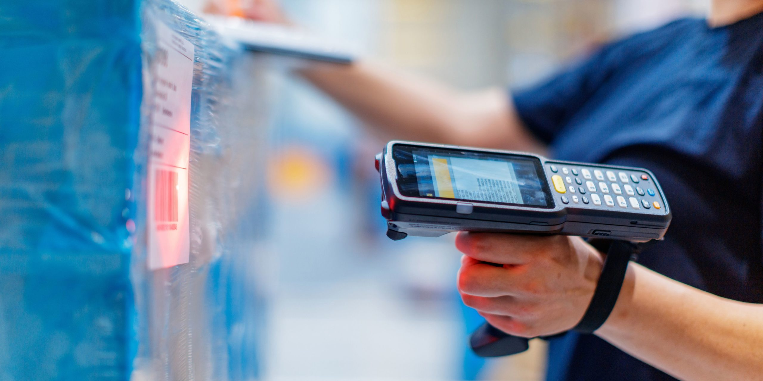 warehouse employee scanning incoming shipment with barcode scanner