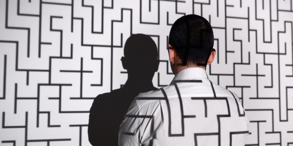 Man looking at projection of maze
