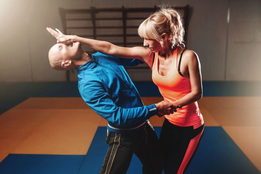 woman demonstrating martial arts on man in gym setting