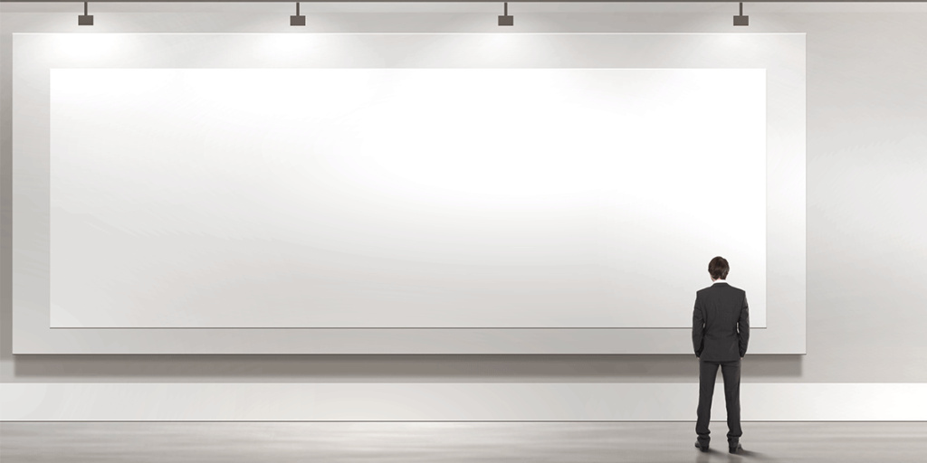 man in suit standing in front of large white canvas on wall