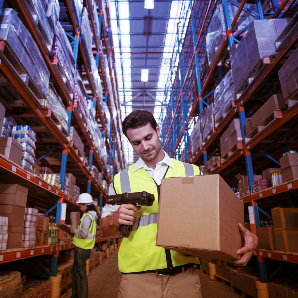 man wearing yellow safety vest in warehouse scanning a box barcode with a hand scanner