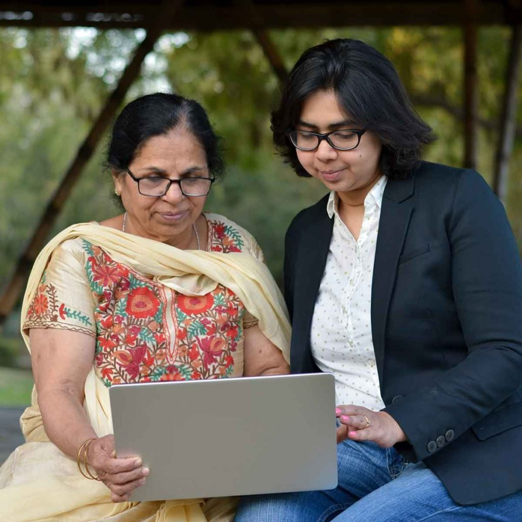 two Indian women, one elderly dressed traditionally, one younger dressed modern, both looking at laptop