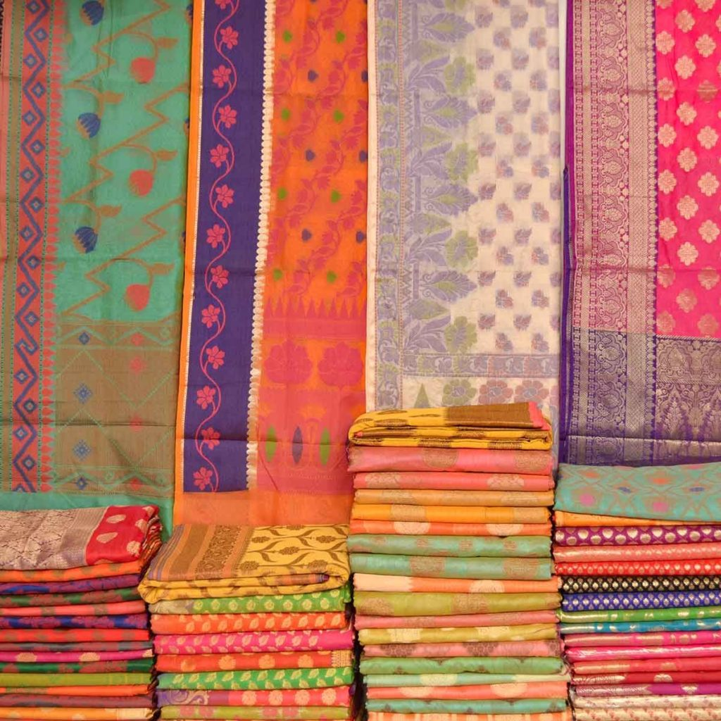 several colorful Indian textiles hanging and folded