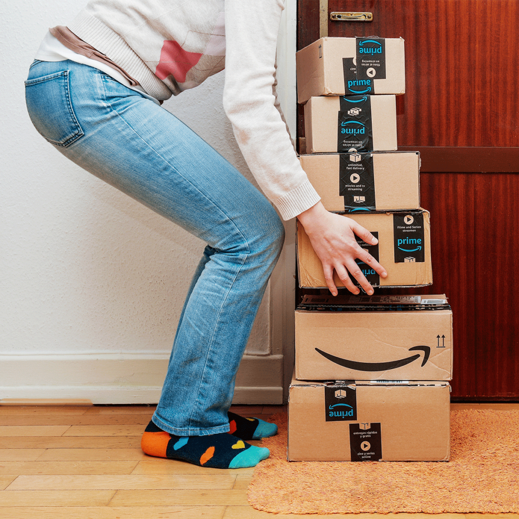 woman picking up stack of amazon fba delivery boxes packages