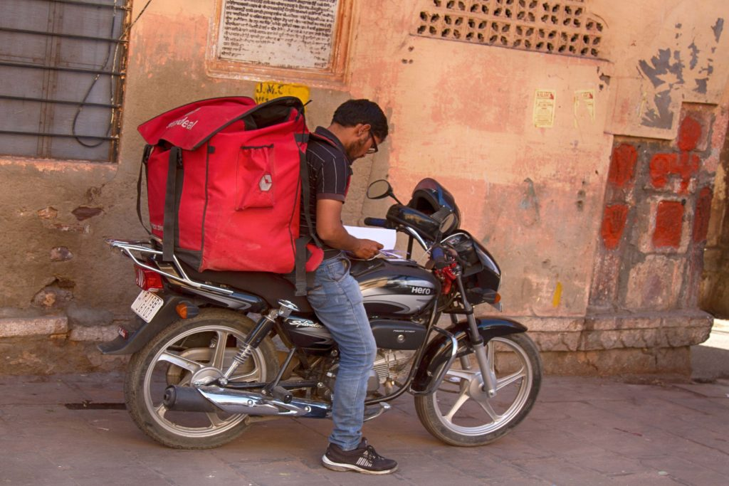 Indian man on delivery bike with red backpack for goods