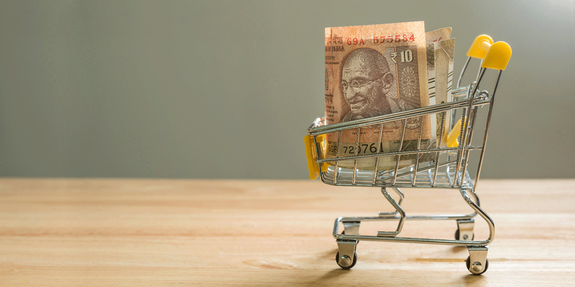 Indian rupee bills in mini shopping cart on a wooden desktop