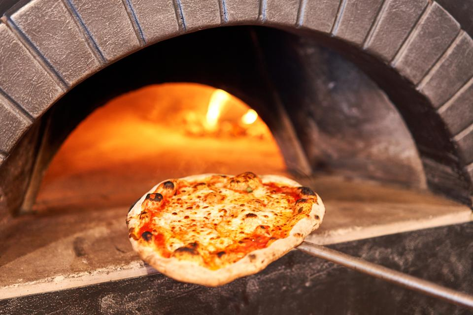 Small artisan pizza on wooden paddle being placed in traditional pizza oven