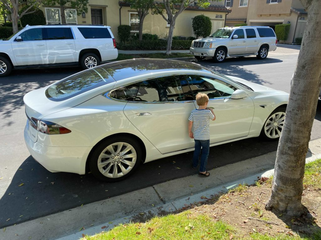Nick's young son Jonas standing outside white Tesla on residential street