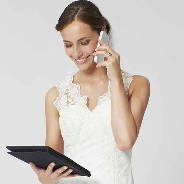 caucasian woman in wedding dress on the phone looking at tablet